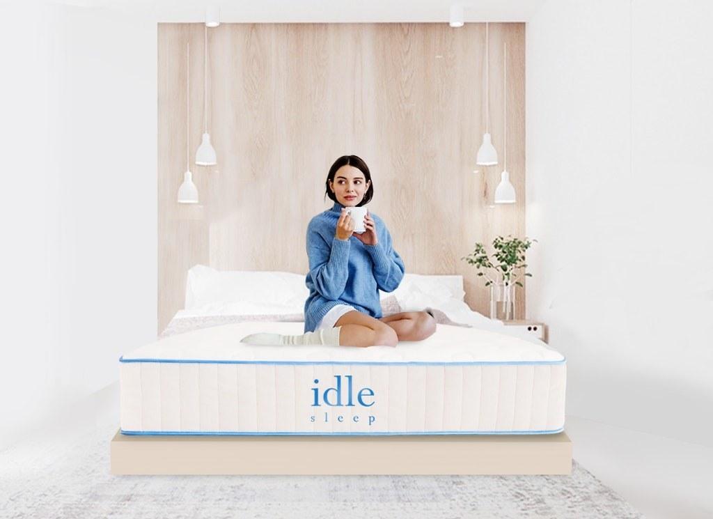 Model sitting on white mattress