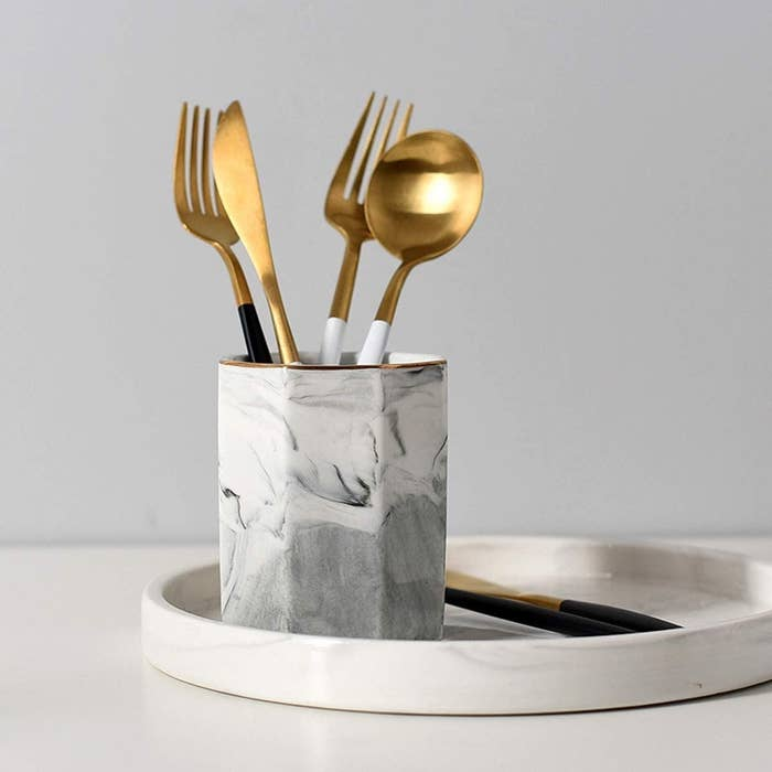 the marble holder with copper utensils inside