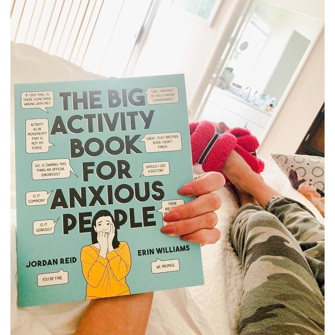 A book called the big activity book for anxious people being held in someones hand