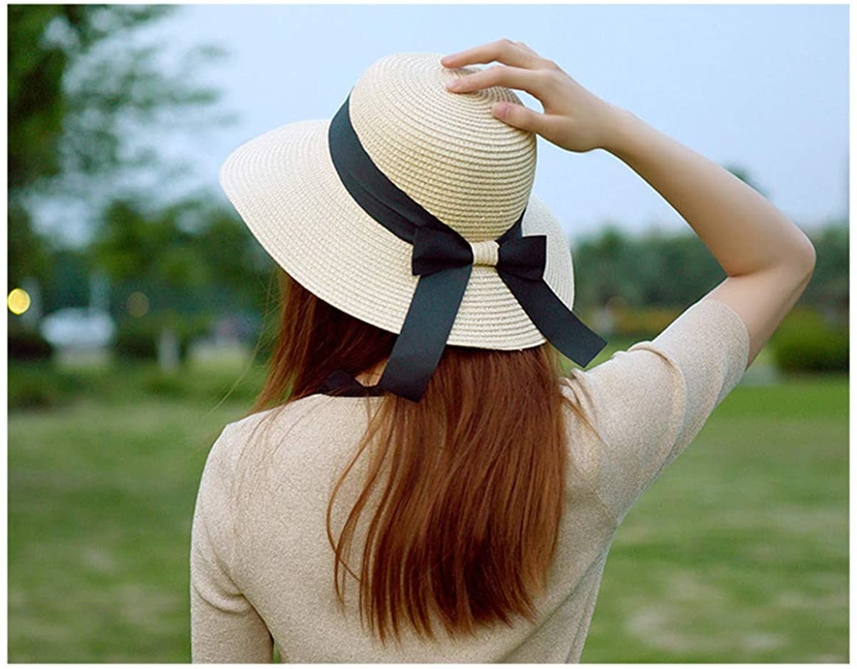 model wearing straw hat with black bow
