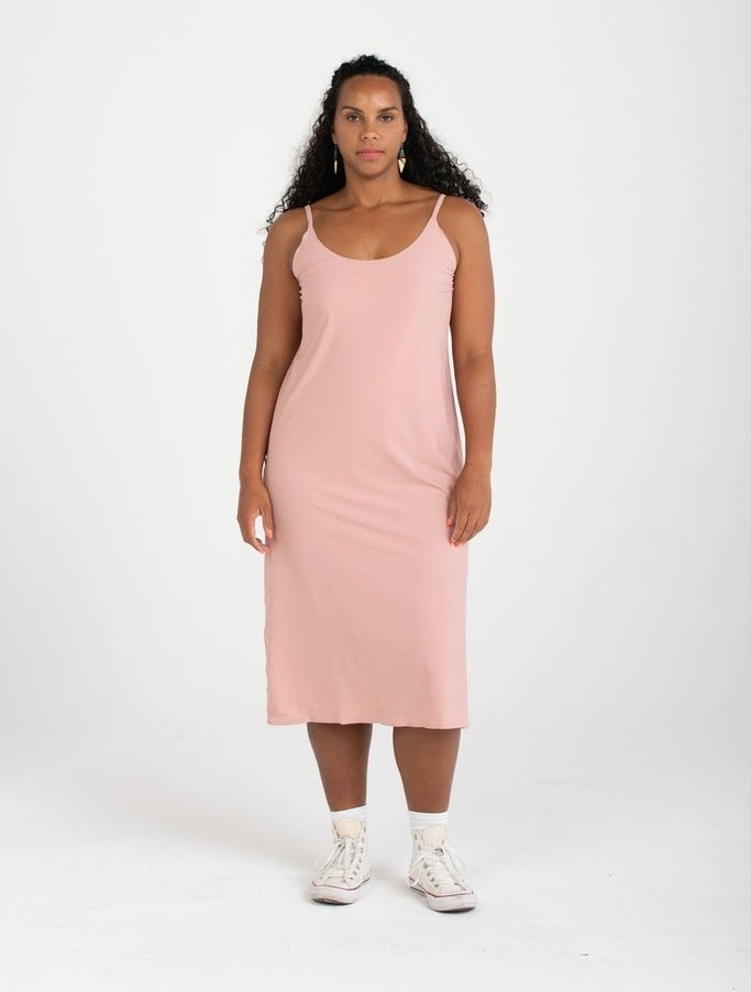 Model wearing the mid-length slip dress with spaghetti straps in light pink
