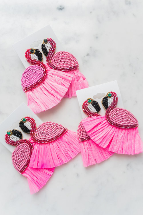 The large earrings, with pink beaded flamingo bodies with tassel details on the bottom and green gemstone eyes
