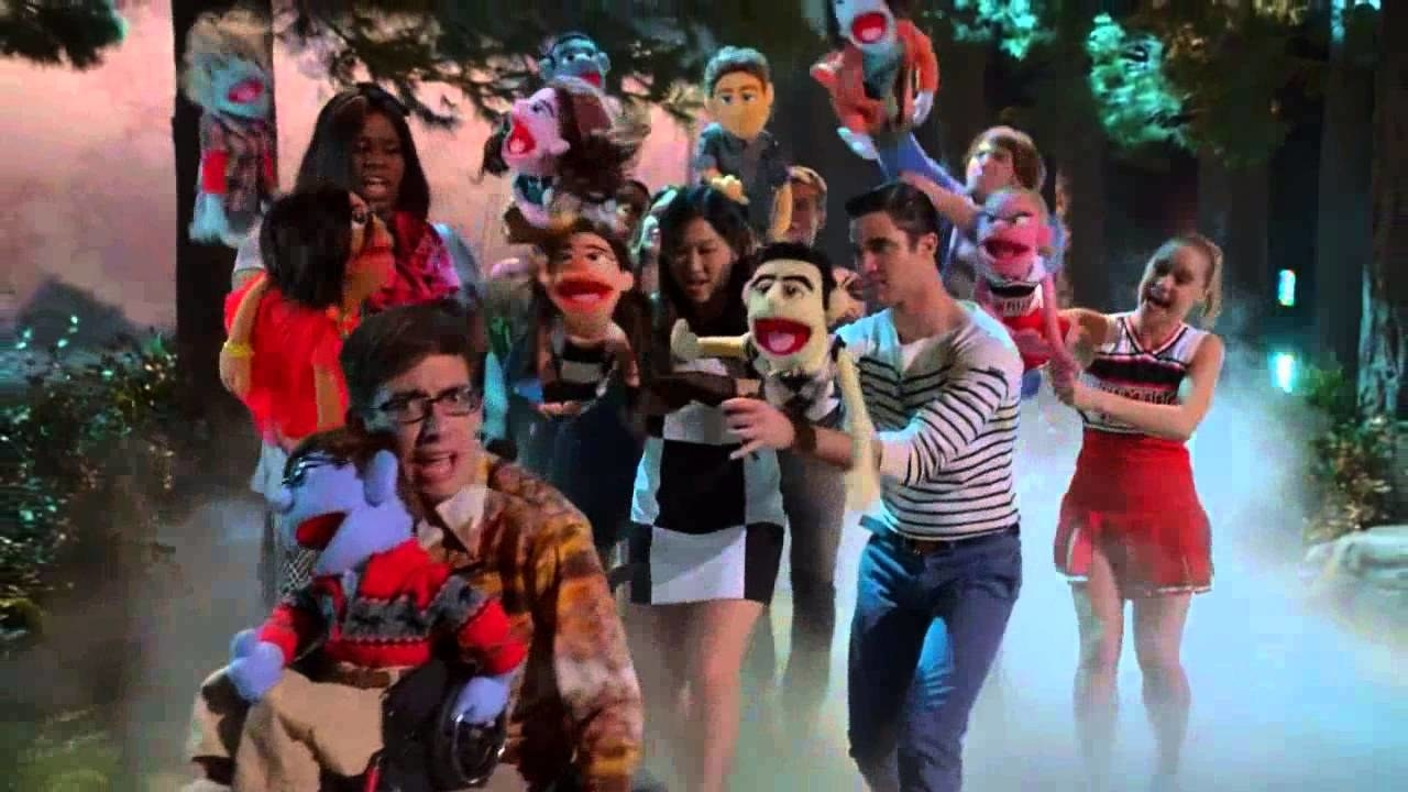 the Glee club dancing holding muppets