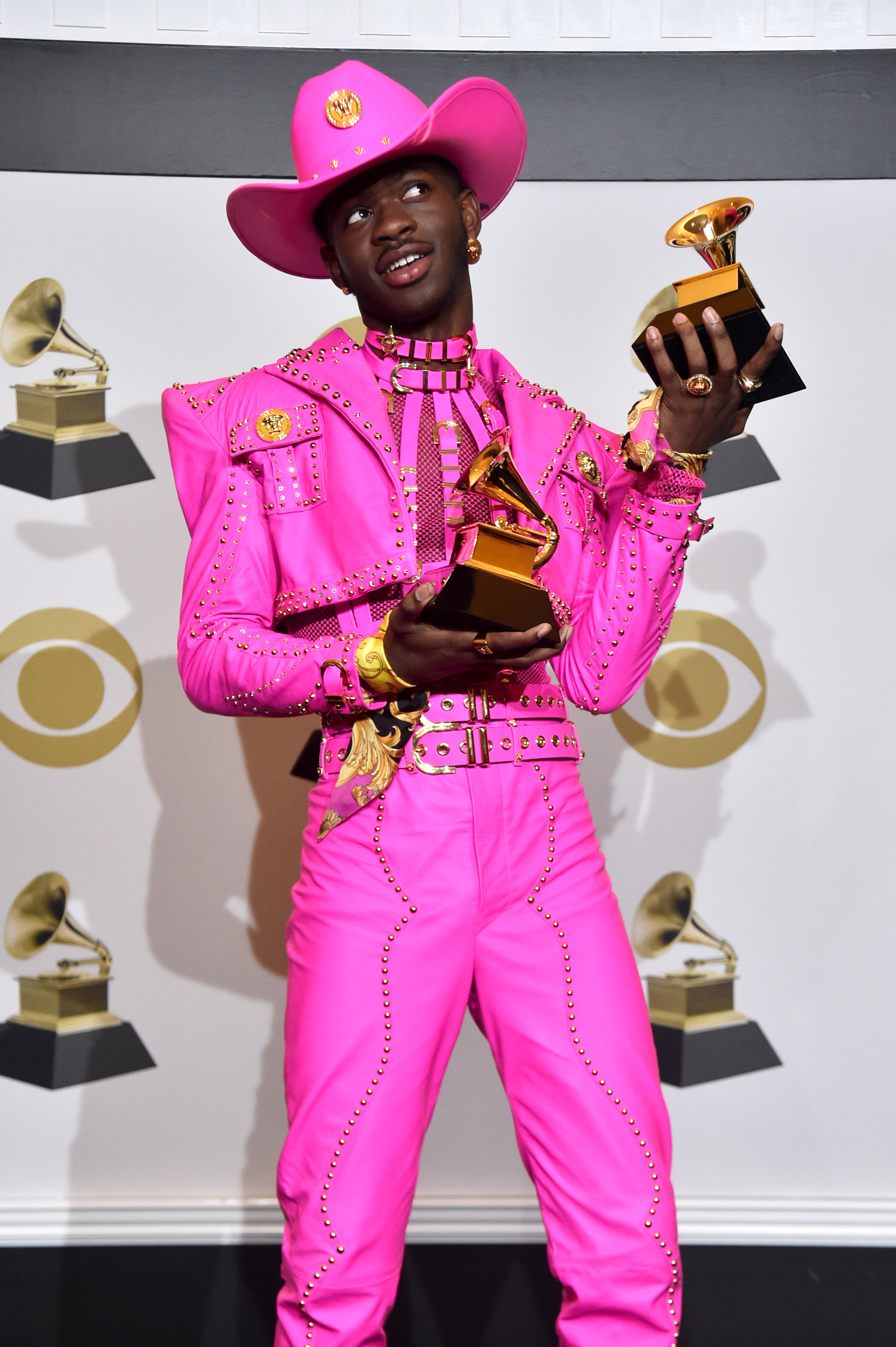 Lil Nas X holds his two Grammy awards wearing a vibrant dominatrix-type outfit and cowboy hat