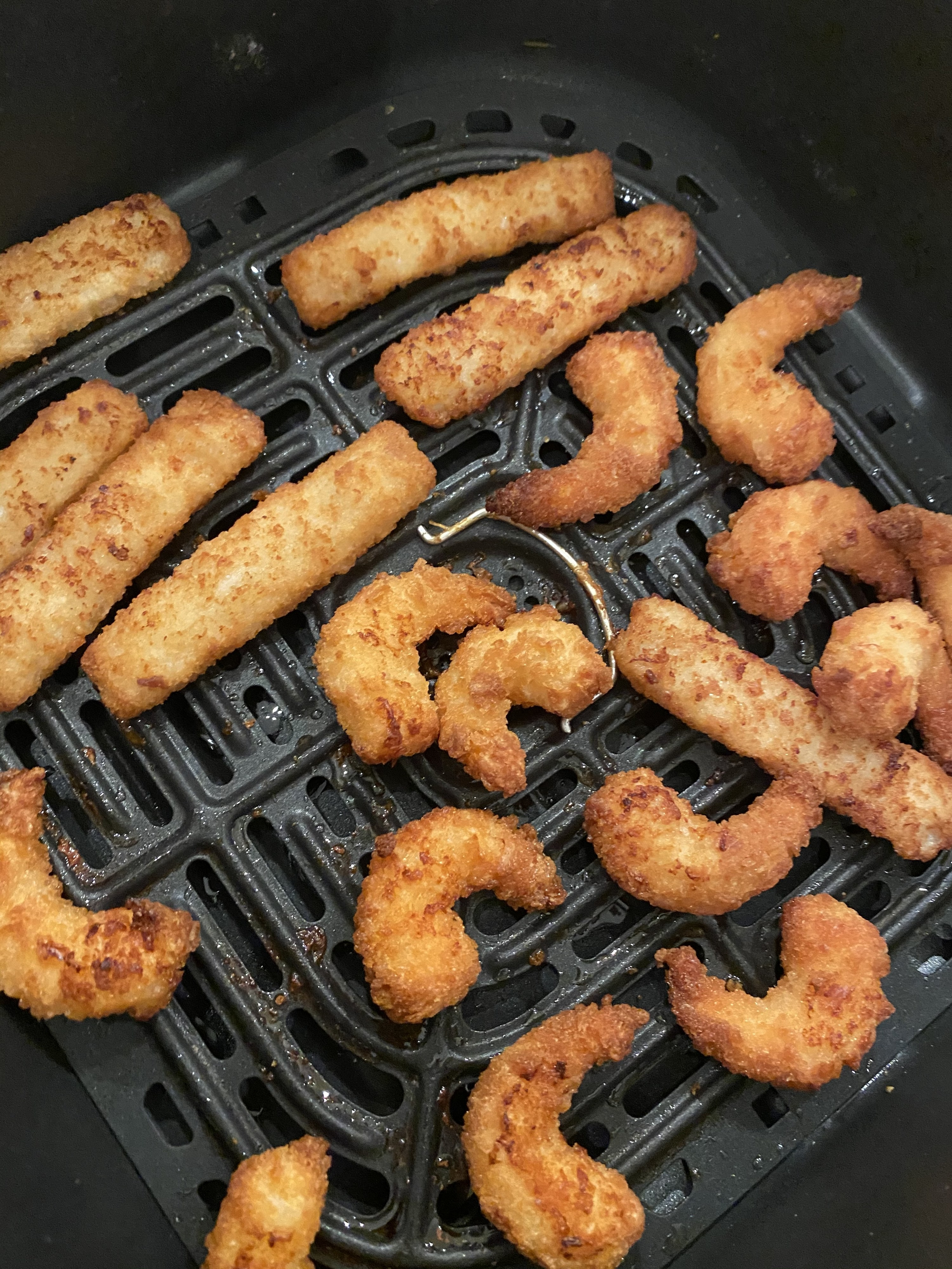 Popcorn shrimp and fish sticks getting golden brown and crispy in an air fryer.