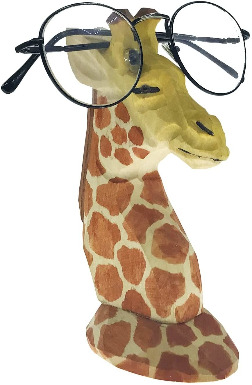A giraffe with a pair of glasses on its head