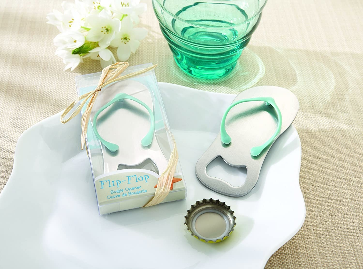 The opener, complete with a 3D flipflop strap, next to a glass and bottle top. There's also another opener next to it, show in the gift-like packaging
