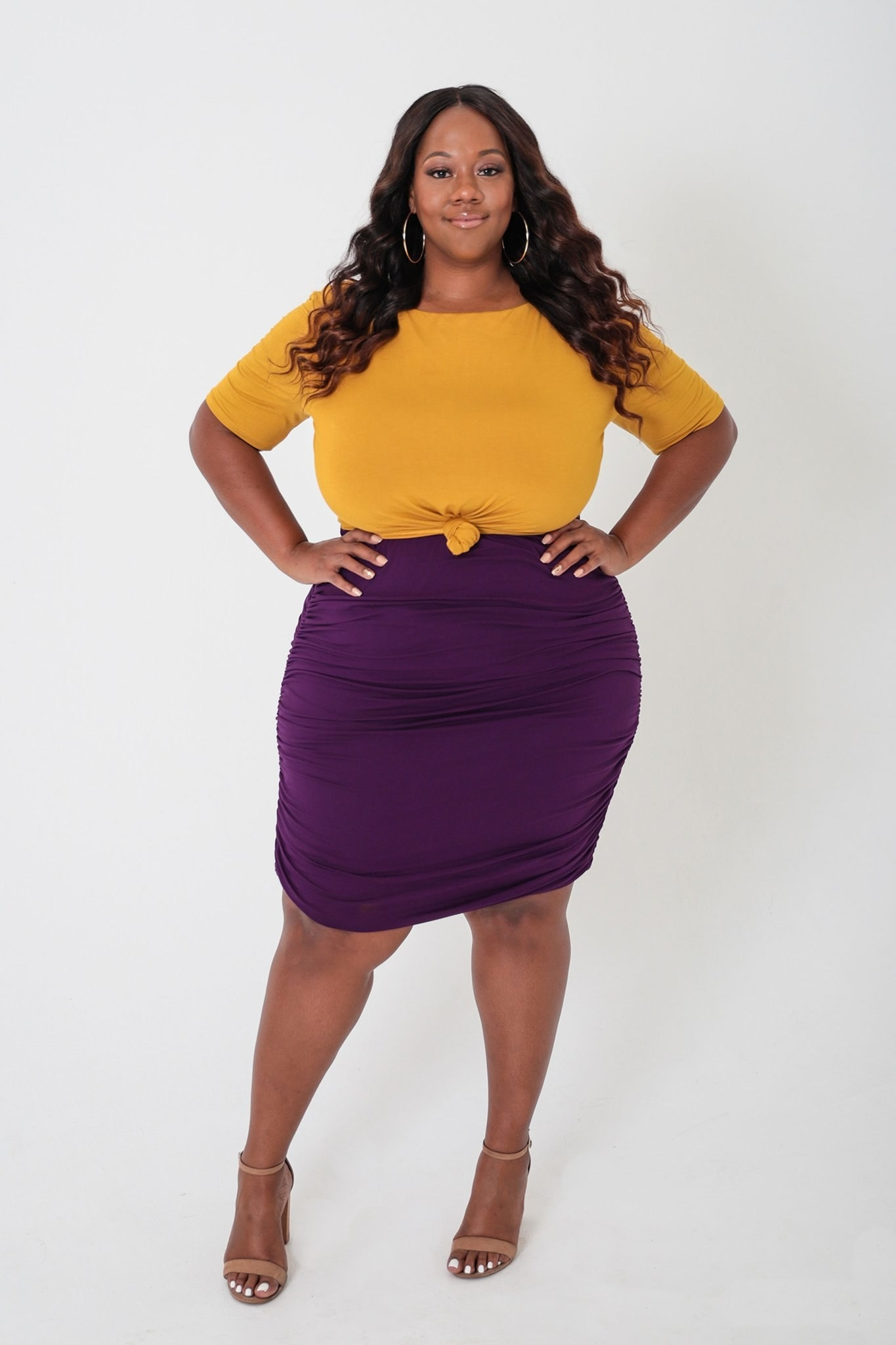 model wearing purple and mustard yellow cocktail dress