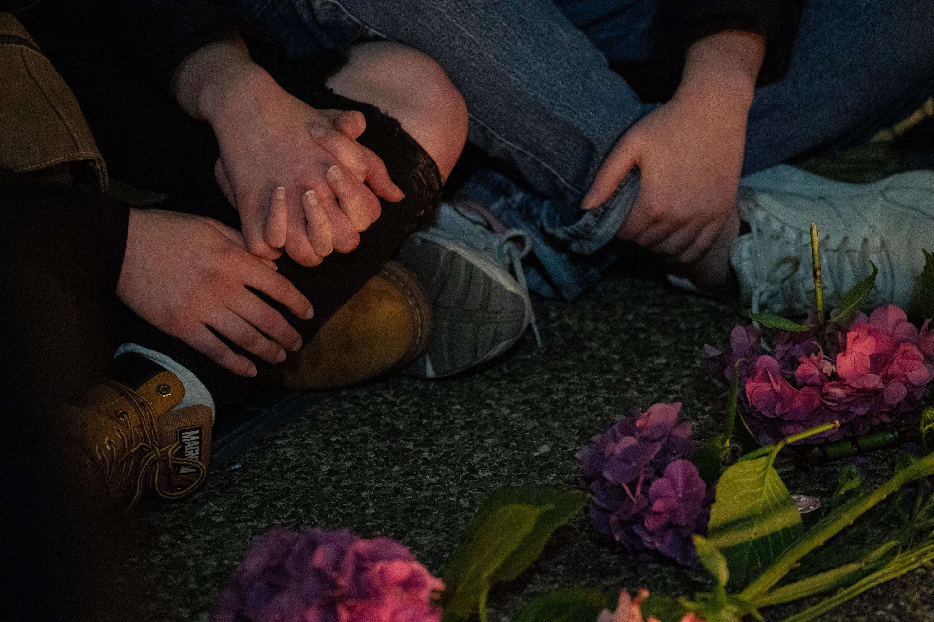 People sitting on the ground hold hands in front of flowers