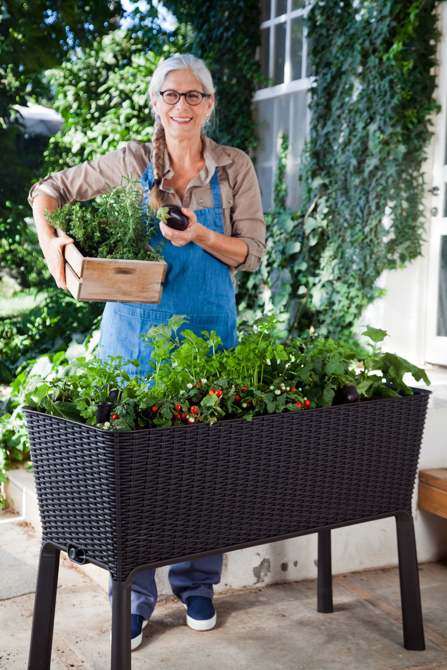 Model standing behind a raised black planter filled with green plants