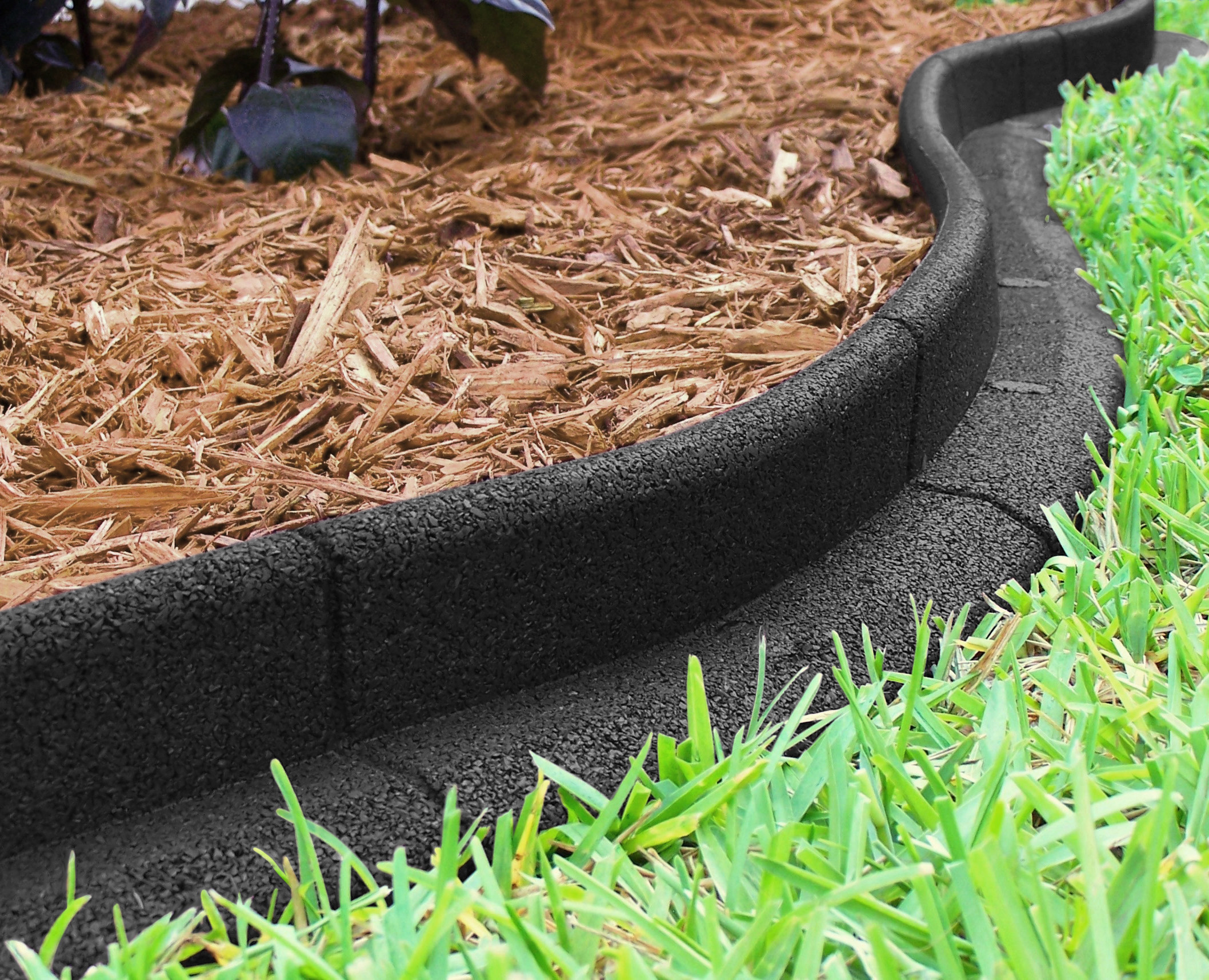 Black landscape edging keeping woodchips from mixing with the lawn