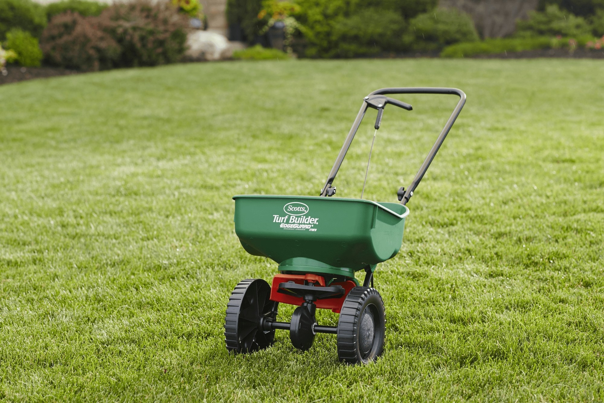 A green spreader with black wheels and handle and red accents