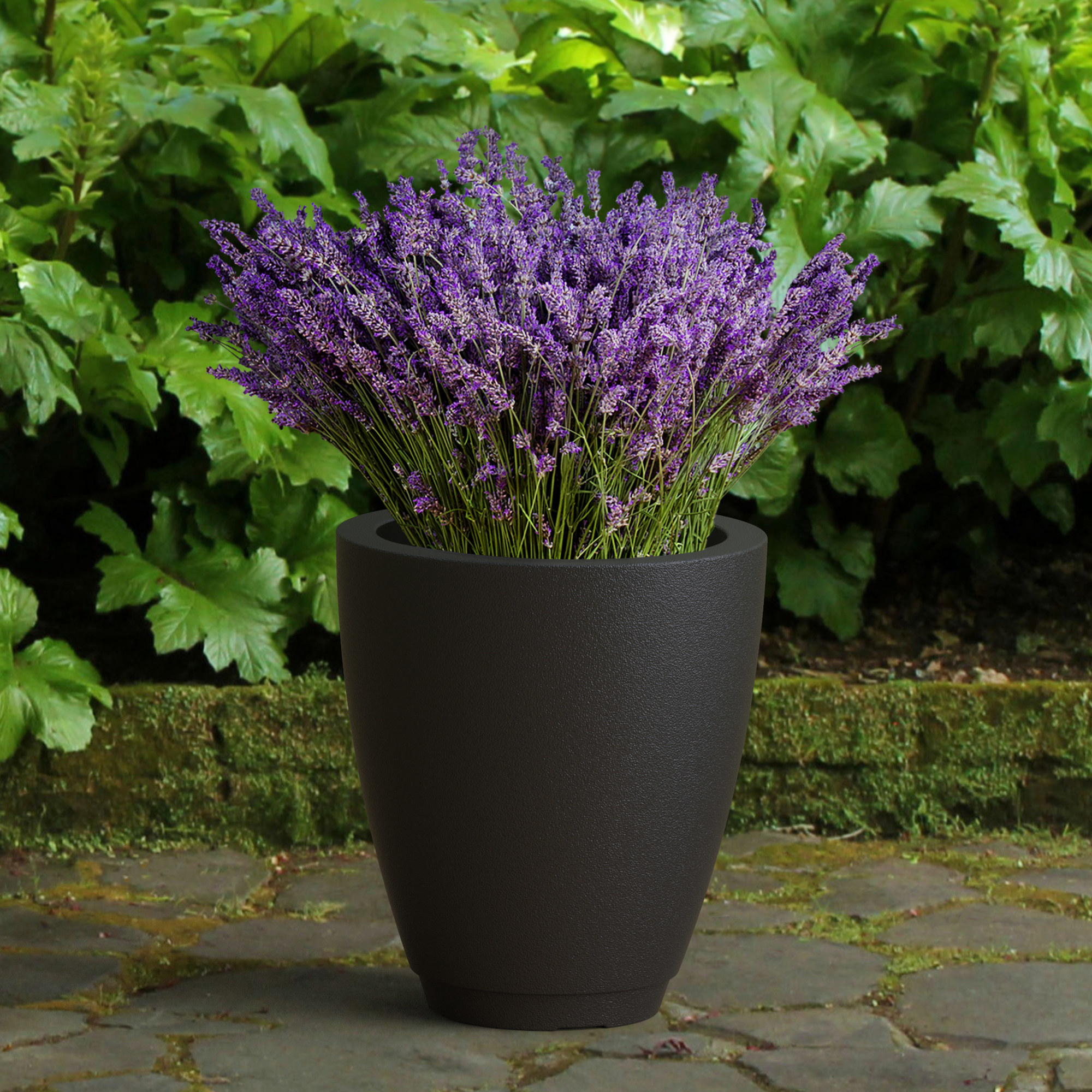 A tall, black, oval-shaped planter with purple flowers inside