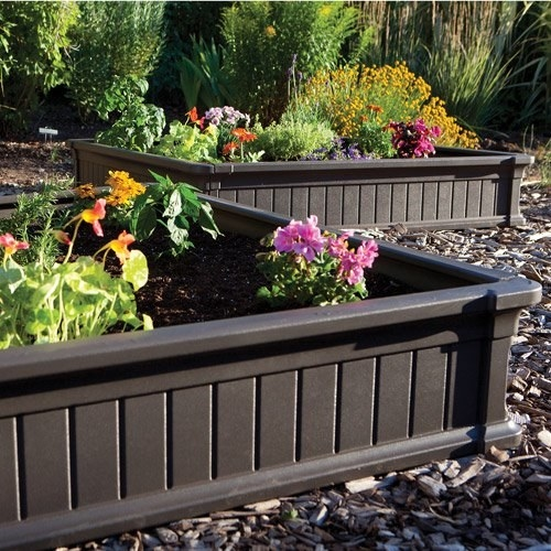 A brown, square-shaped raised garden bed with colorful flowers planted inside