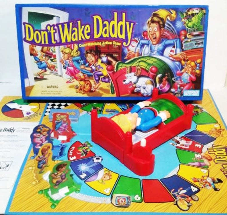 The Don't Wake Daddy board game set up with the box for it behind it.