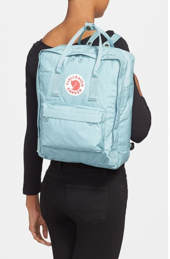 model with back facing camera carrying a light blue backpack