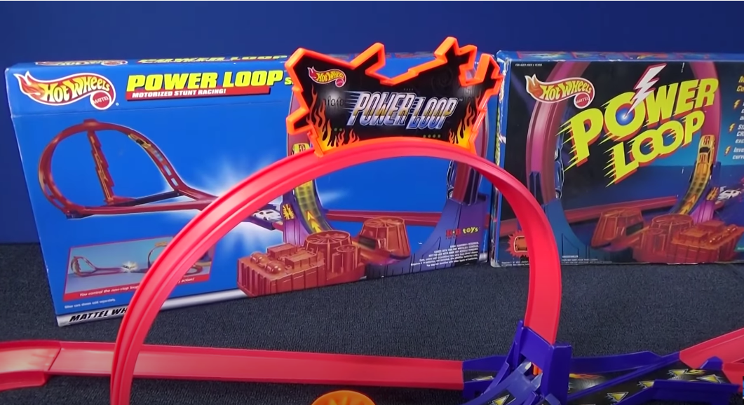 A red Matchbox Power Loop built, with two boxes for it in the background