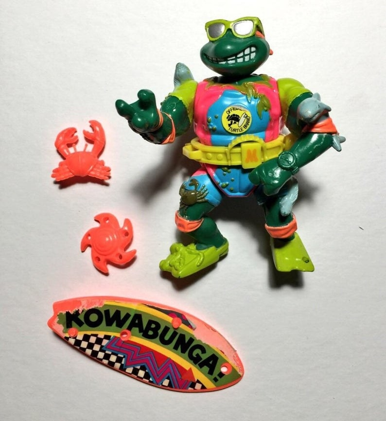 A Michelangelo action figure dressed as a surfer and wearing sunglasses