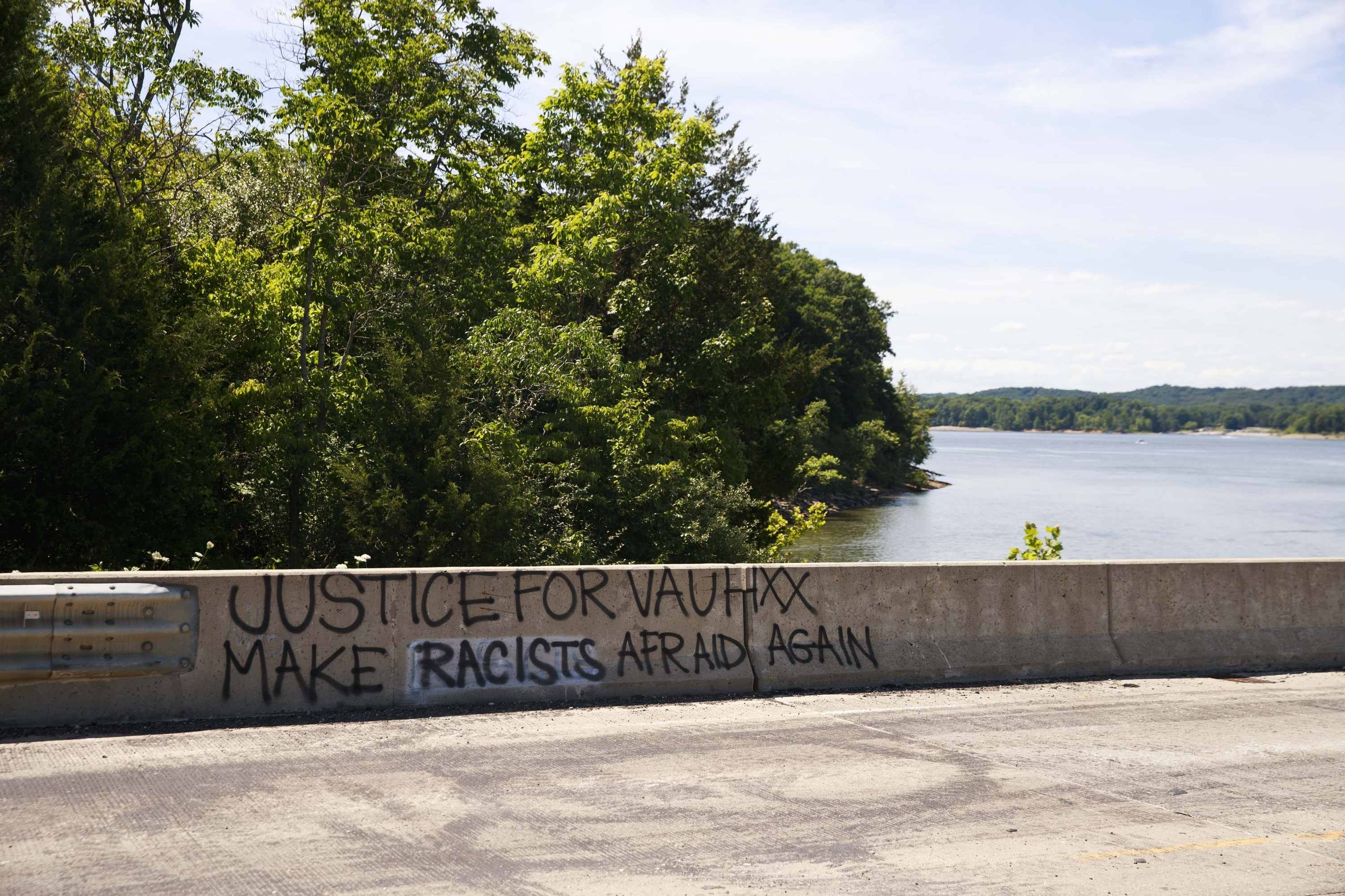 "Graffiti saying ""Justice for Vauhxx, make racists afraid again"" is painted on a road barrier next to a lake with trees near where Booker was allegedly assaulted"