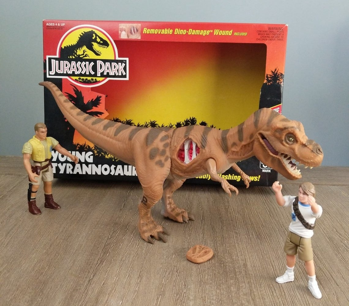 "A T-Rex toy with its ""dino-damage wound"" showing while next to two different Jurassic Park human action figures."