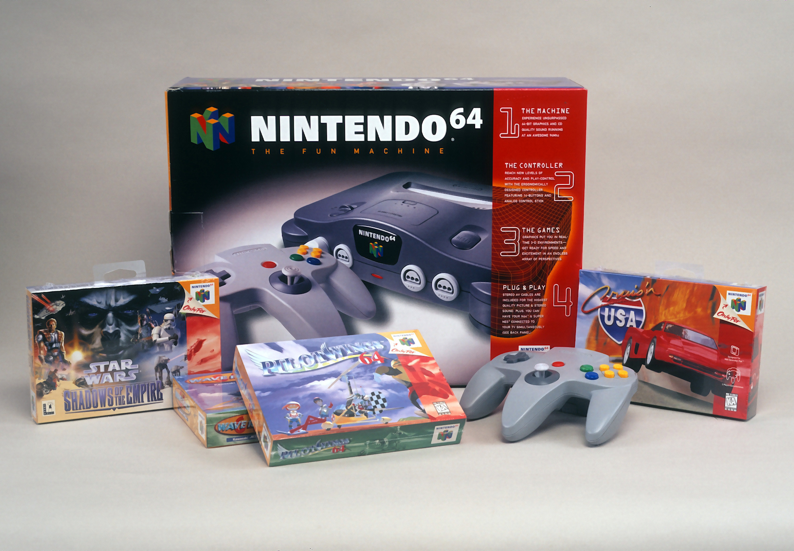 A product shot of a Nintendo 64 box alongside a controller for it and four different games