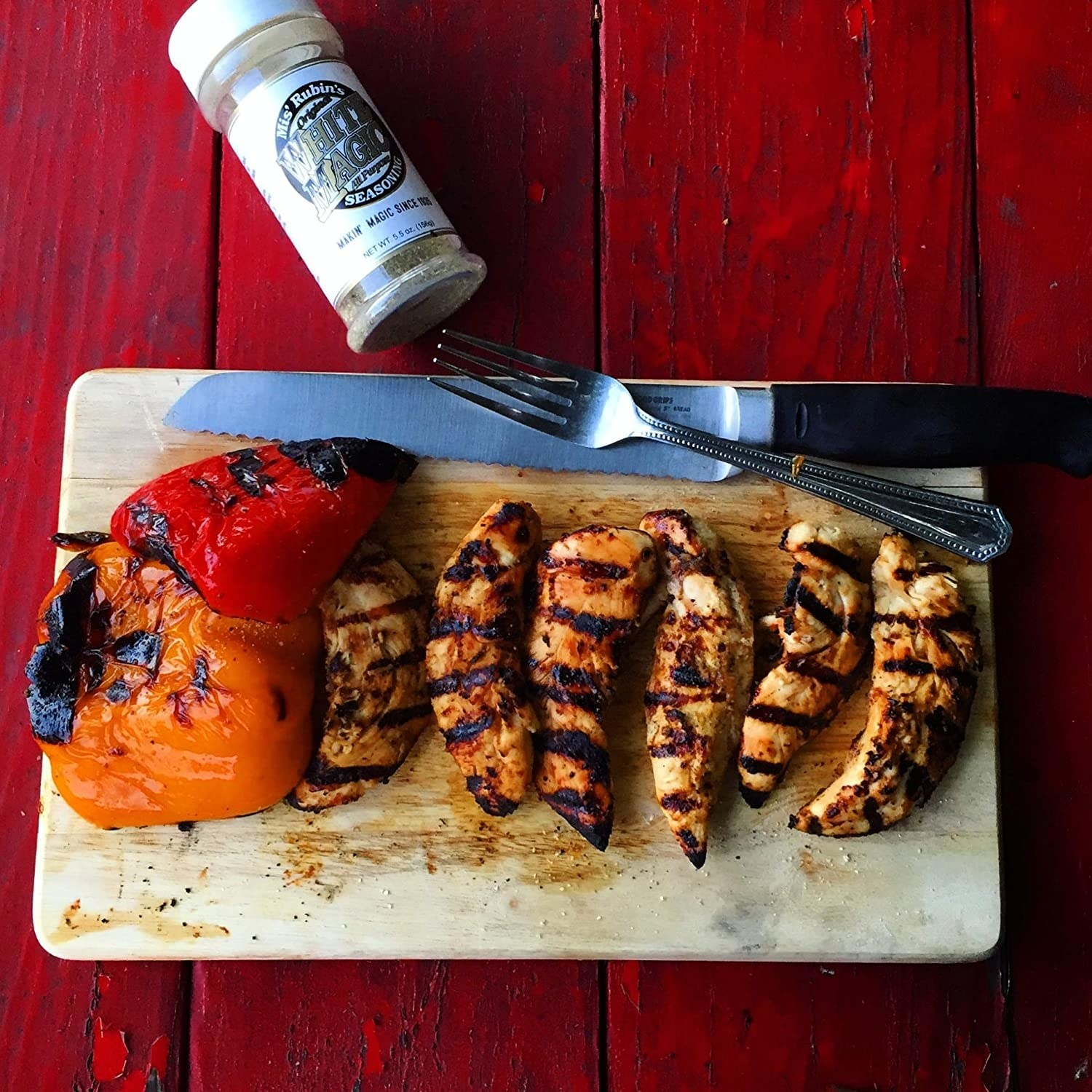 A bottle of Magic Dry Rub Spice Powder next to a plate of grilled chicken.