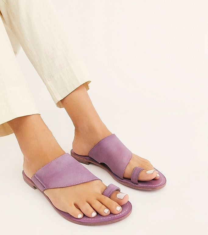 model's feet with light purple leather sandals with strap across foot and a toe loop