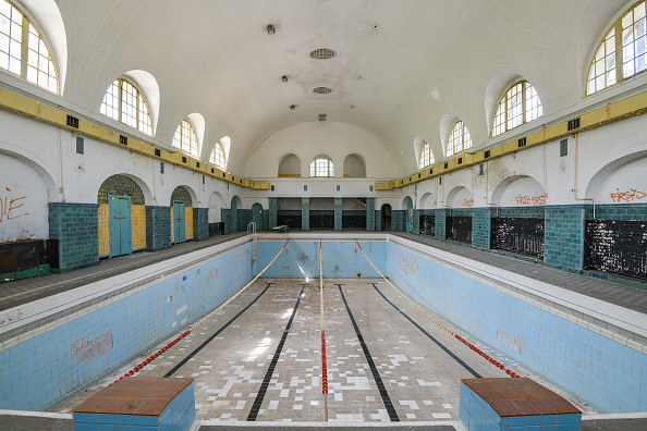 Empty pool in a long gymnasium with high ceilings, broken tiles, and graffiti