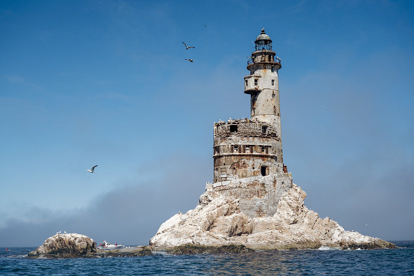 old abandoned lighthouse in the middle of the sea on a rock, birds flying around it