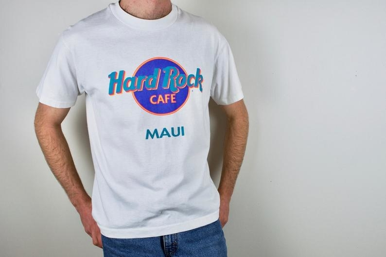Photo of a man wearing a '90s white Hard Rock Cafe: Maui T-shirt with teal and purple lettering.