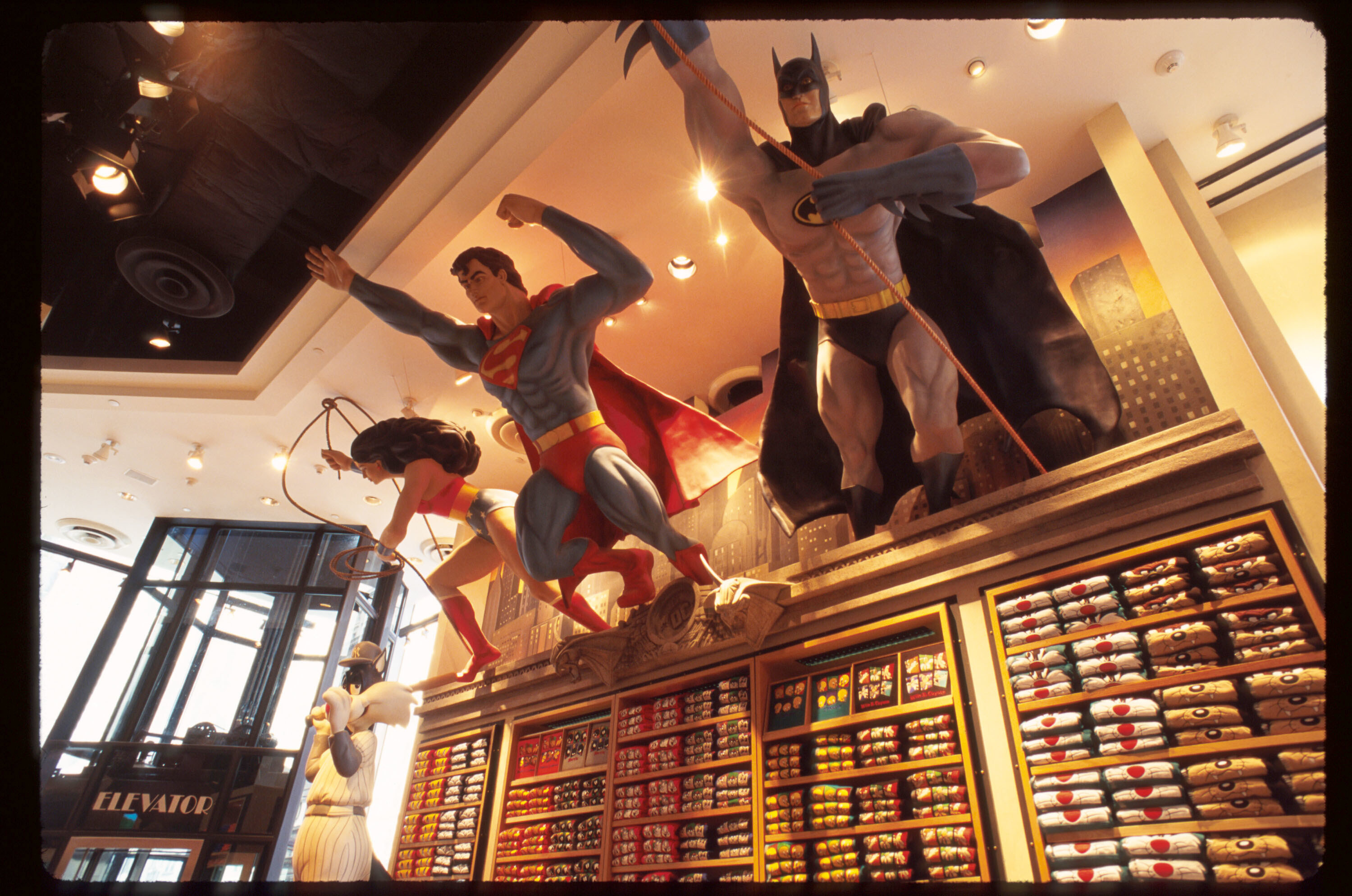 Large statues of Wonder Woman, Superman, and Batman leaping out of the wall inside a Warner Bros. Studio Store.