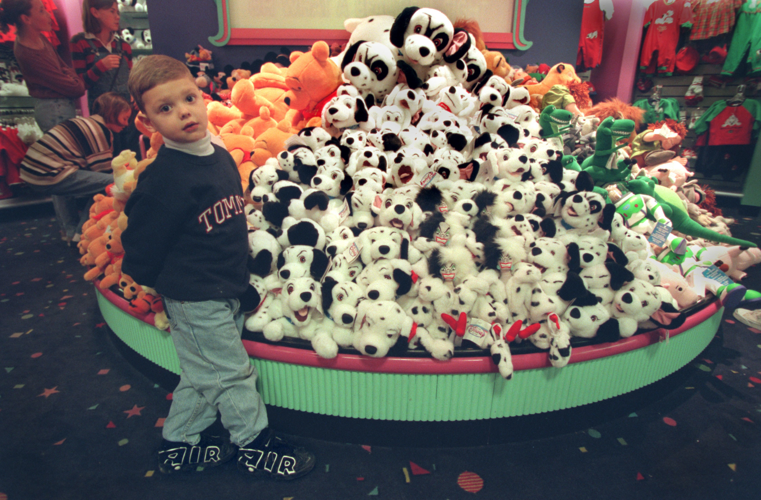 A kid standing next to a stack of 101 Dalmatians stuffed animals in the back of a Disney Store.
