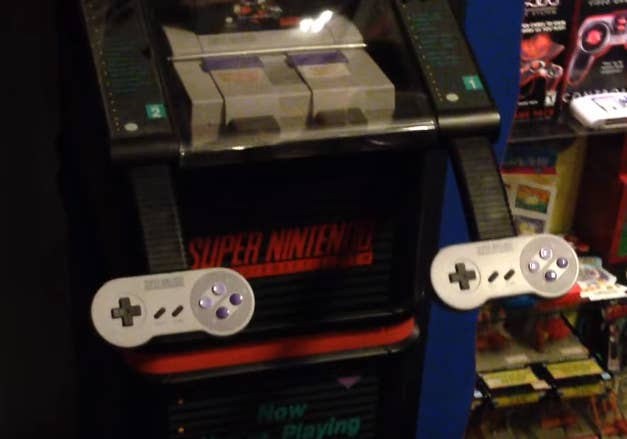 A close-up of two Super Nintendo controllers that are part of a SNES video game display.