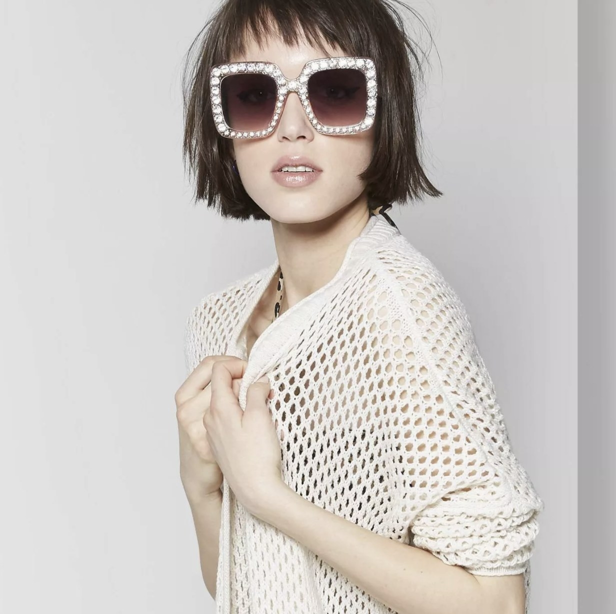 A pair of pink squared-shaped sunglasses with a dark ombre tint on the lens