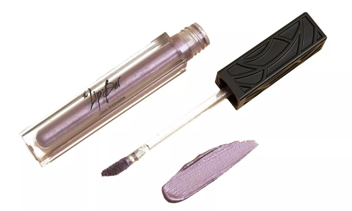 A glossy purple-tinted eye shadow with an applicator