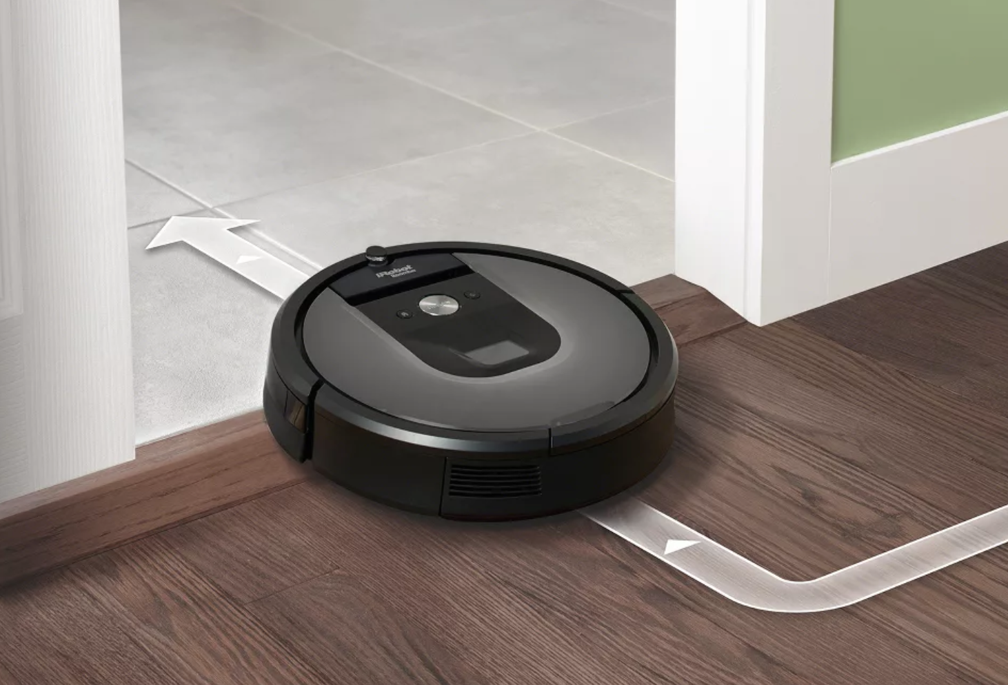 A gray circle-shaped Roomba on a hardwood floor