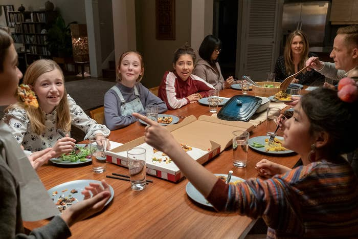 The cast of The Babysitter's Club sits around the dinner table eating pizza and salad, and laughing and smiling at each other.