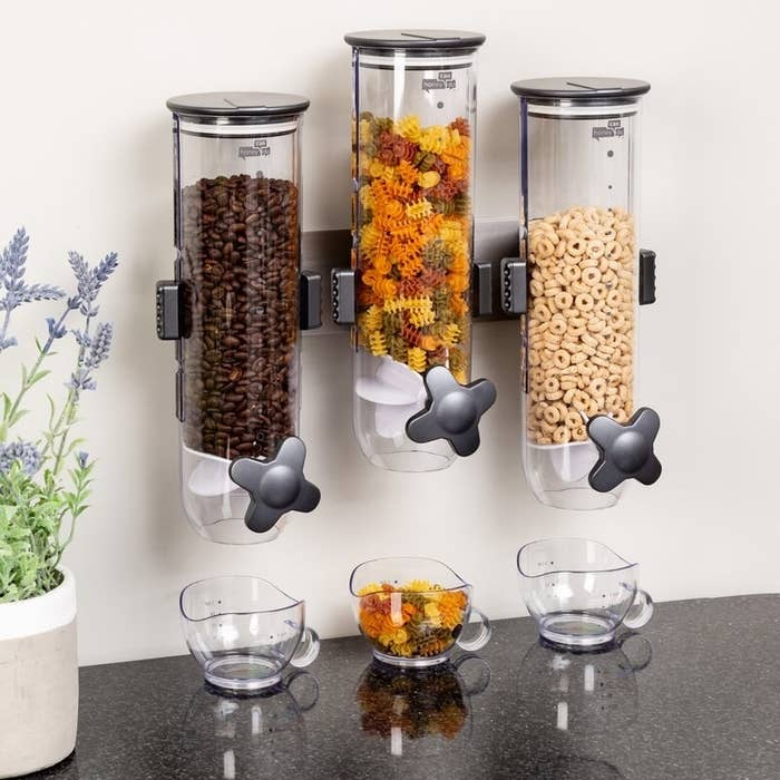 The three-dispenser set mounted to the wall and full of cereal, pasta, and coffee beans
