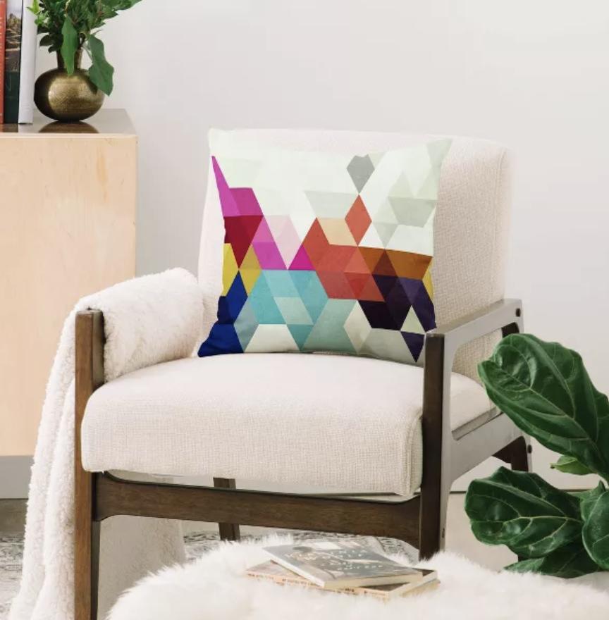 A rainbow geometric throw pillow on a chair