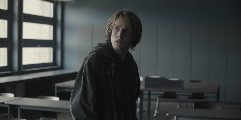 """Louis Hofmann as Jonas sitting in an empty classroom in Season 3, Episode 1 of """"Dark"""""""