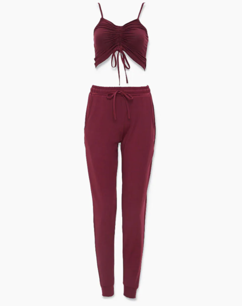 A pair of red drawstring joggers with a matching red strapped cropped tank with a cinched seam in the middle