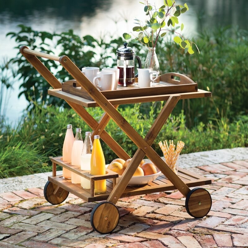 wood cart with two levels holding food and drinks