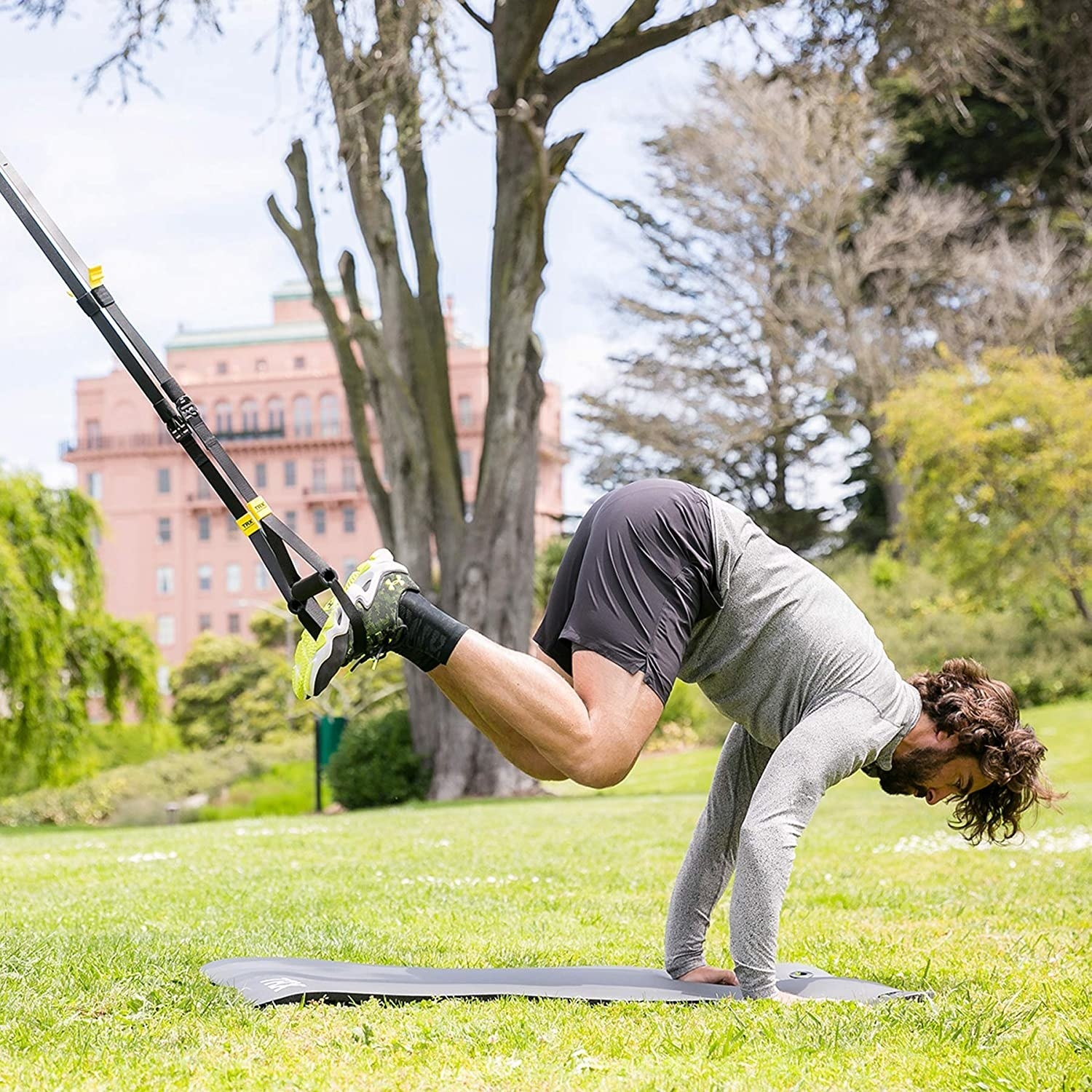 A model with their feet around the elevated TRX straps and their arms on a yoga mat. The straps are attached to a tree and they are lifting their bodyweight with their arms while pulling down with their legs.