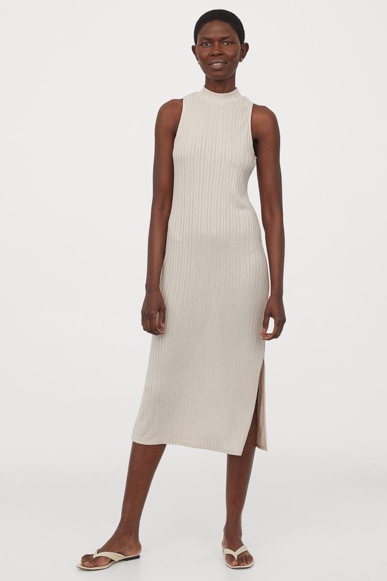 model wearing high-neck light beige midi dress with slit