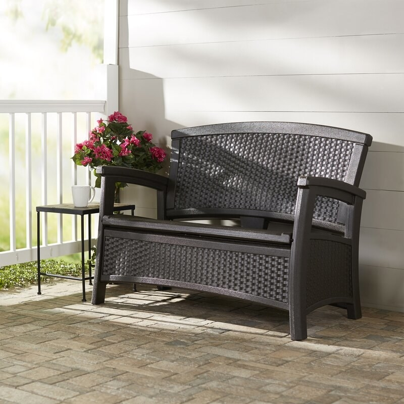 black woven-looking bench on porch