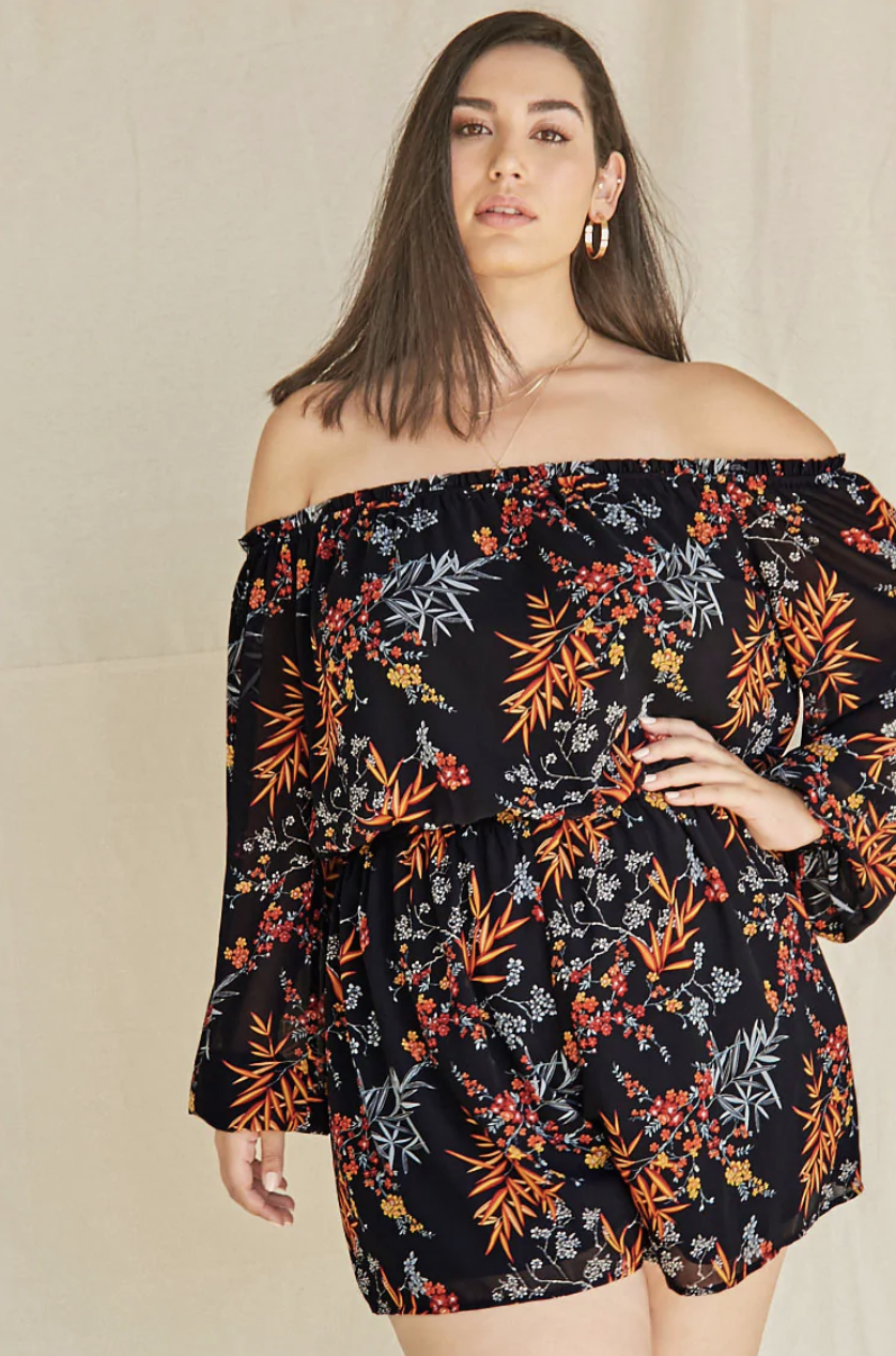 A model in the black floral romper, which has shorts and long sleeves