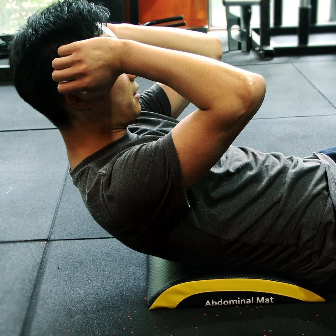 A model doing crunches with the abdominal mat supporting their back, giving them a wider range of motion as they move down during the crunch