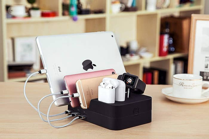 An iPad, two iPhones, two sets of AirPods and an Apple watch charging on the dock