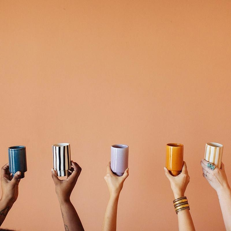 models hold up cups with small stands in blue, black and white striped, lavender, burnt orange, and orange striped
