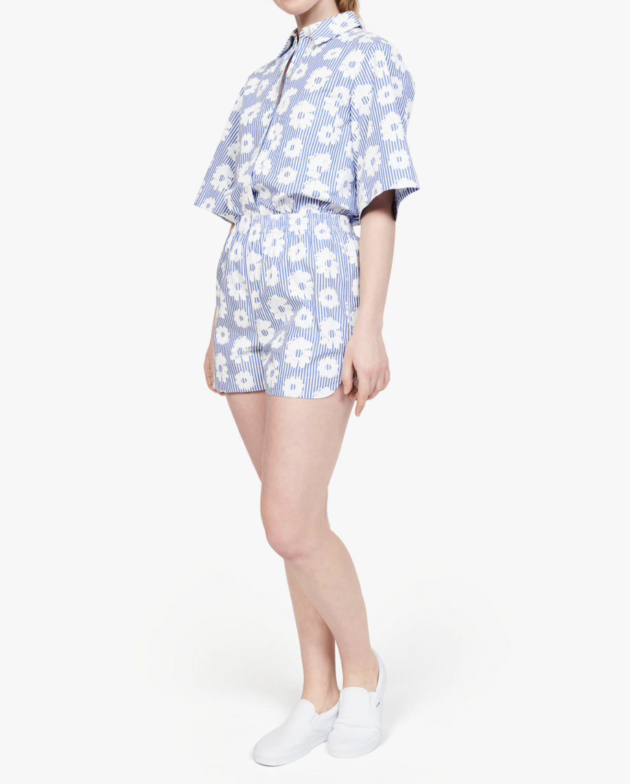 a model wearing the high waisted pull-on shirts in light blue with white stripes and white embroidered daisies